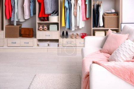 Photo for Cozy sofa and big wardrobe in dressing room - Royalty Free Image