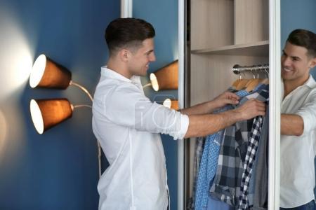 Foto de Hombre recogiendo camisa del armario. Armario de moda - Imagen libre de derechos