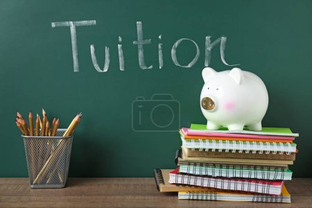 Photo for Chalkboard with word TUITION and piggy bank on notebooks - Royalty Free Image