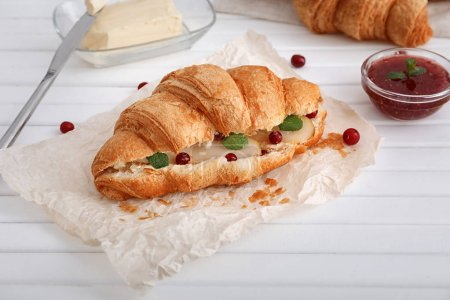 Tasty croissant with filling on wooden table