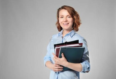 Beautiful real estate agent with documents on grey background