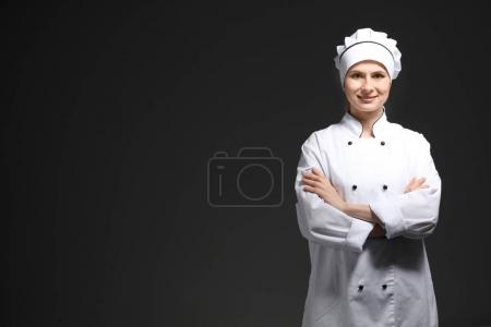 Photo for Female chef in uniform on black background - Royalty Free Image