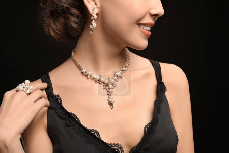 Beautiful young woman with elegant jewelry on dark background, closeup
