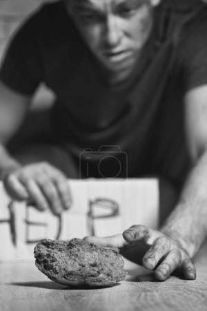 Homeless poor man picking up piece of bread from floor