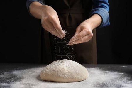 Woman sprinkling flour over fresh dough on table