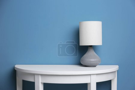 Photo for Elegant lamp on table near color wall - Royalty Free Image