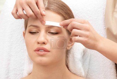 Photo pour Jeune femme à subir une procédure de correction des sourcils au salon - image libre de droit