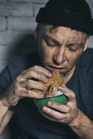 Hungry poor man eating piece of bread against brick wall