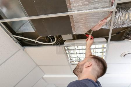 Male technician repairing industrial air conditioner indoors