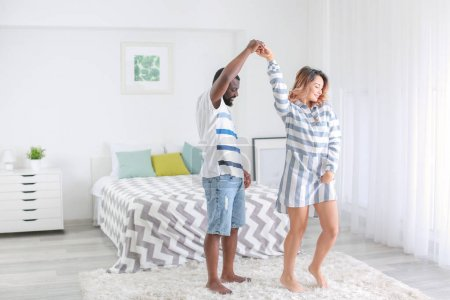 Photo pour Joli couple interracial, danse à la maison - image libre de droit
