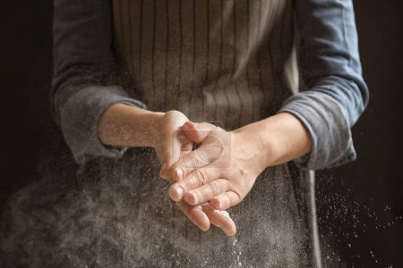 Woman clapping hands and sprinkling flour on black background