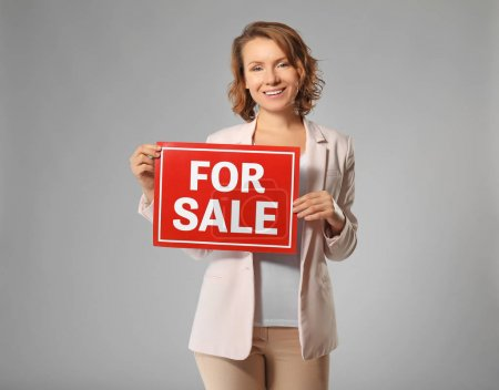 "Beautiful real estate agent with ""For sale"" sign on grey background"