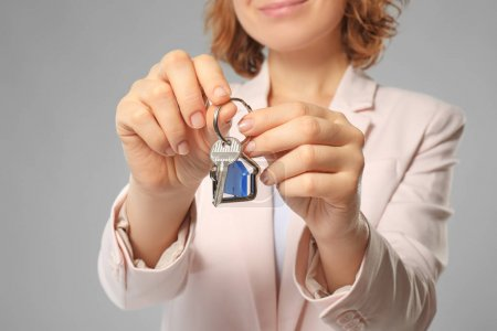 Beautiful real estate agent with key on grey background, closeup