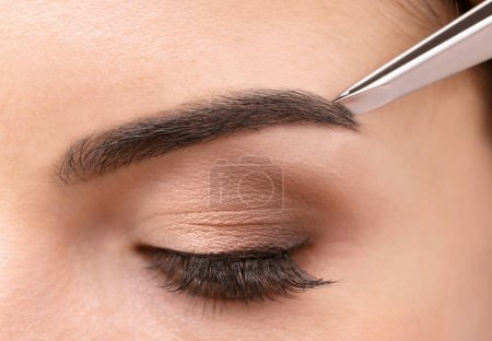 Photo for Young woman correcting shape of eyebrows, closeup - Royalty Free Image