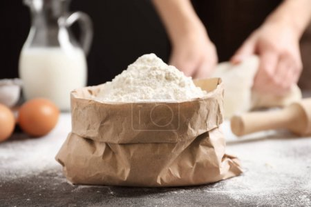 Paper bag with flour and woman making dough on background