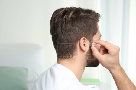 Photo pour Jeune homme mettre la prothèse auditive dans l'oreille à l'intérieur - image libre de droit