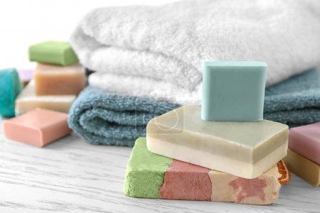 Photo pour Serviettes douces et différentes barres de savon sur la table - image libre de droit