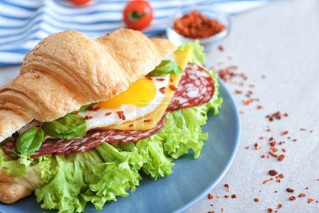 Photo pour Plaque avec sandwich savoureux croissants sur table - image libre de droit