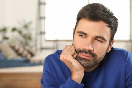 Young bearded man in casual clothes indoors