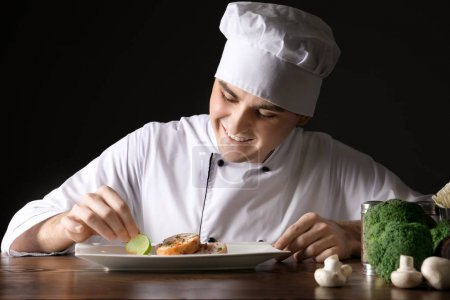 Male chef in uniform garnishing tasty dish against black background