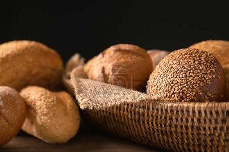 Wicker basket with different bread on table against dark background, closeup