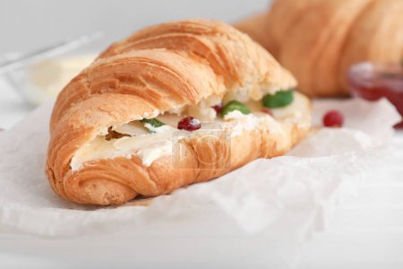 Tasty croissant with filling on table