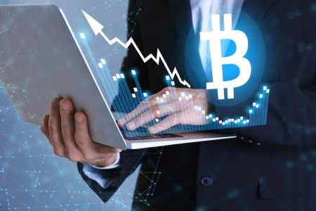 Bitcoin rate and businessman using laptop on color background