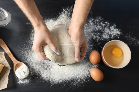 Photo for Man kneading dough on table sprinkled with flour - Royalty Free Image