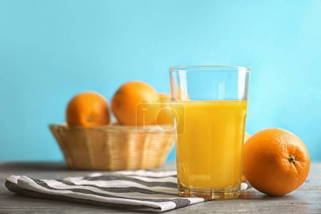 Glass of fresh orange juice with fruit on table against color background