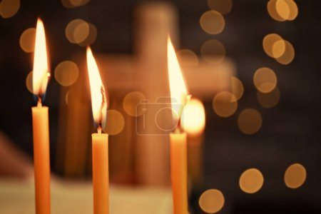 Burning candles and blurred cross on background