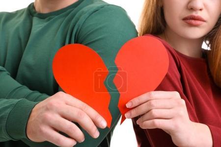 Photo pour Jeune couple tenant des moitiés de cœur brisé sur fond blanc. Problèmes relationnels - image libre de droit