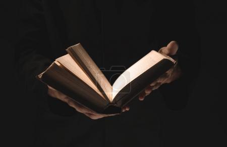 Photo pour Prêtre avec la vieille Bible sur fond noir, gros plan - image libre de droit