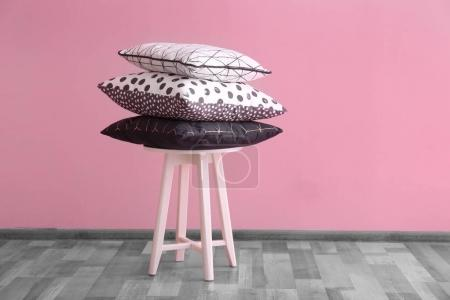 Stack of pillows on stool near color wall