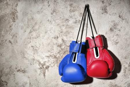Photo pour Gants de boxe rouges et bleus accroché sur le mur. Concept de confrontation politique entre le major américain parties - démocrate et républicain - image libre de droit