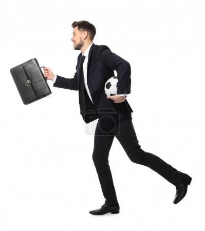 Jeune homme d'affaires avec le ballon de soccer et porte-documents en cours d'exécution sur fond blanc