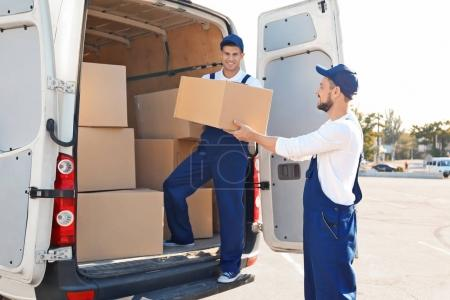 Delivery men unloading moving boxes from car