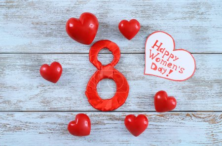 """Number 8, decorative hearts and greeting card with words """"Happy Women's Day"""" on wooden background"""