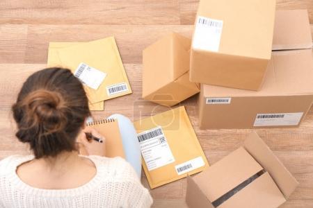 Photo pour Startupper femme préparent des colis pour l'expédition aux clients à l'intérieur - image libre de droit