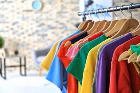 Photo for Rack with rainbow clothes on hangers indoors - Royalty Free Image
