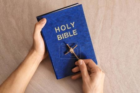 Religious man with handmade cross and Bible on light background