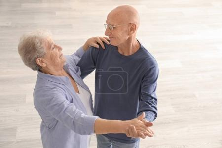 Cute elderly couple dancing in empty room