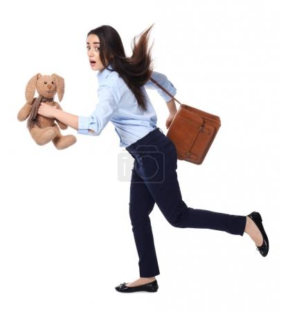 Young businesswoman with bag and bunny toy running on white background