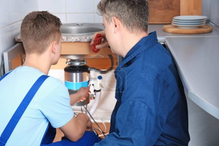 Plumber with young trainee repairing sink in kitchen