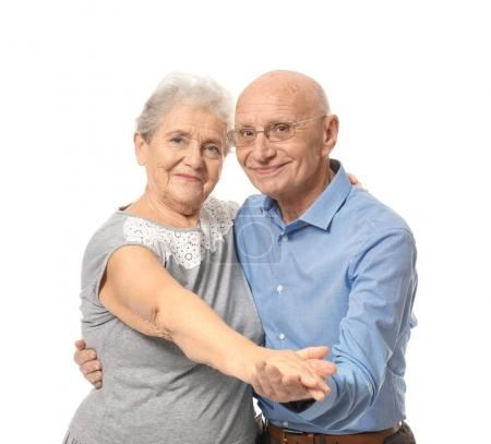 Cute elderly couple dancing against white background