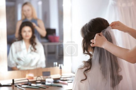 Hairdresser preparing bride before her wedding in room