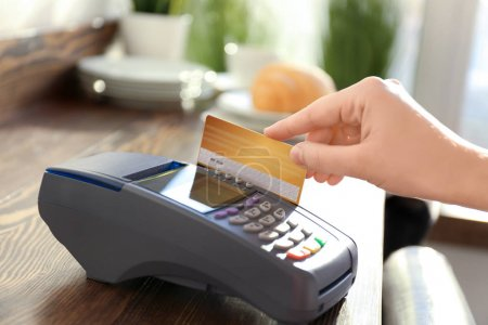 Woman using bank terminal for credit card payment on wooden table
