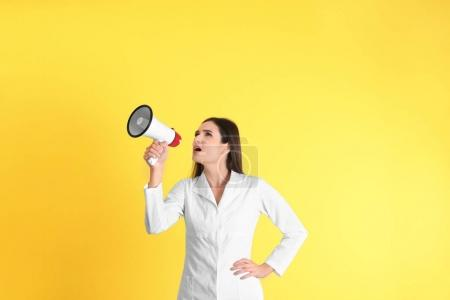 Female doctor with megaphone on yellow background