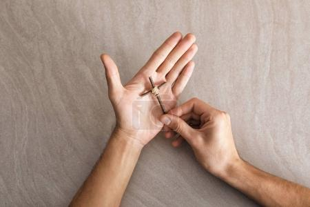 Religious young man holding handmade cross over table