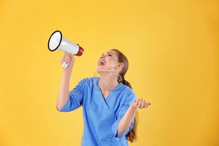 Young female doctor with megaphone on yellow background