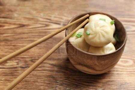 Bowl with tasty baozi dumplings on wooden background